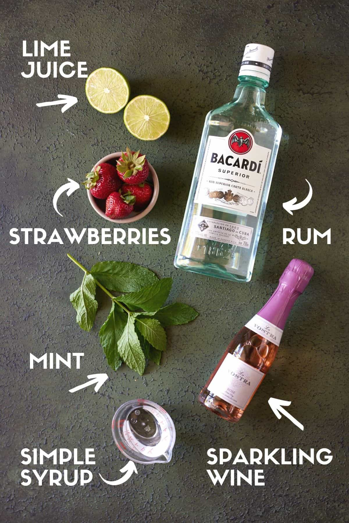 Ingredients for strawberry mojitos, including strawberries, mint, limes, rum and sparkling rosé wine.