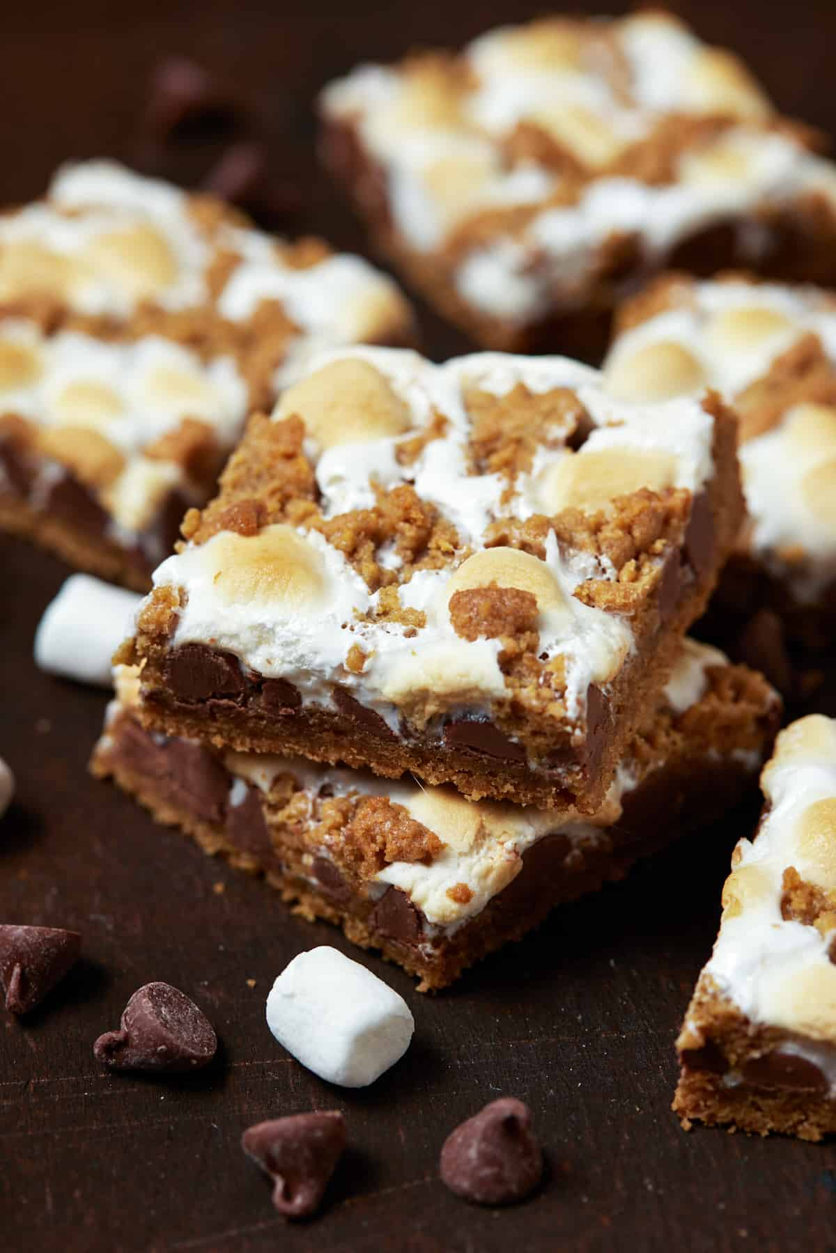 A short stack of baked s'mores bars on a dark wood board.