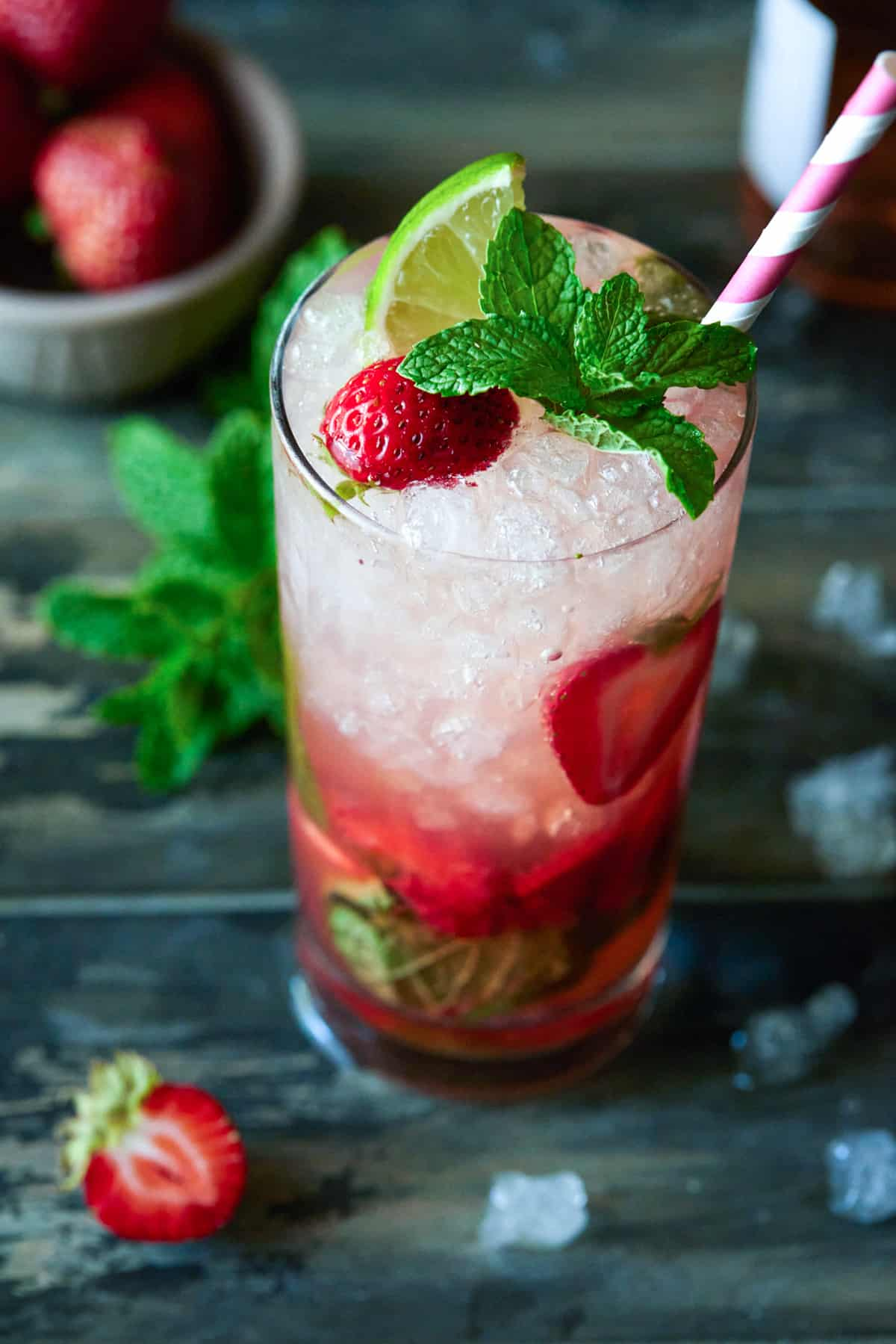 Strawberry mojito in a highball glass garnished with fresh lime, strawberry and mint leaves.