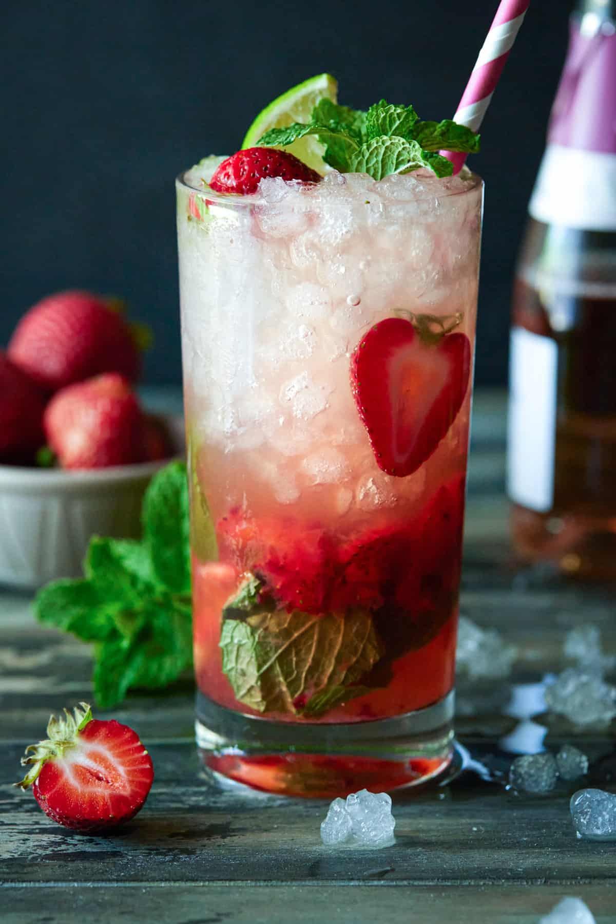 Highball glass filled with Strawberry Mojito. Garnished with limes, strawberries and mint leaves.