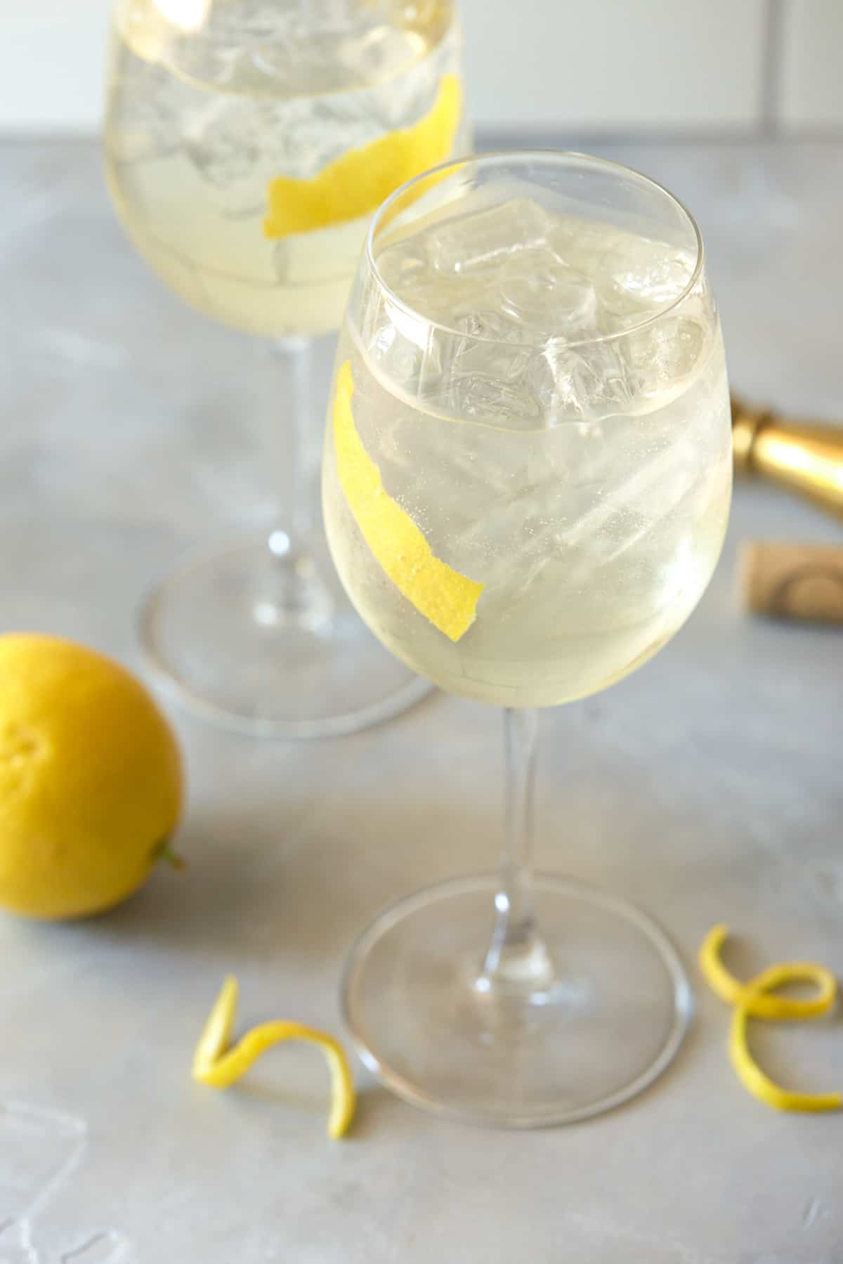 Wine glasses filled with drink and garnished with lemon peel.