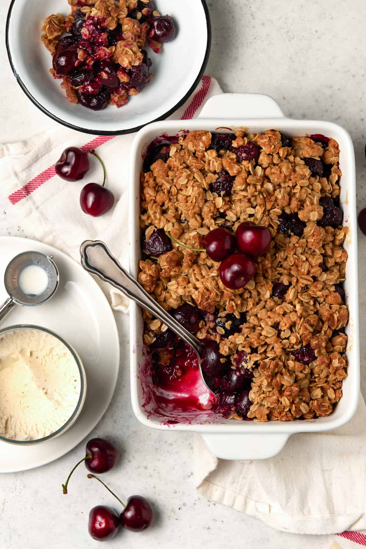 Cherry crisp in a white casserole dish with a serving removed.