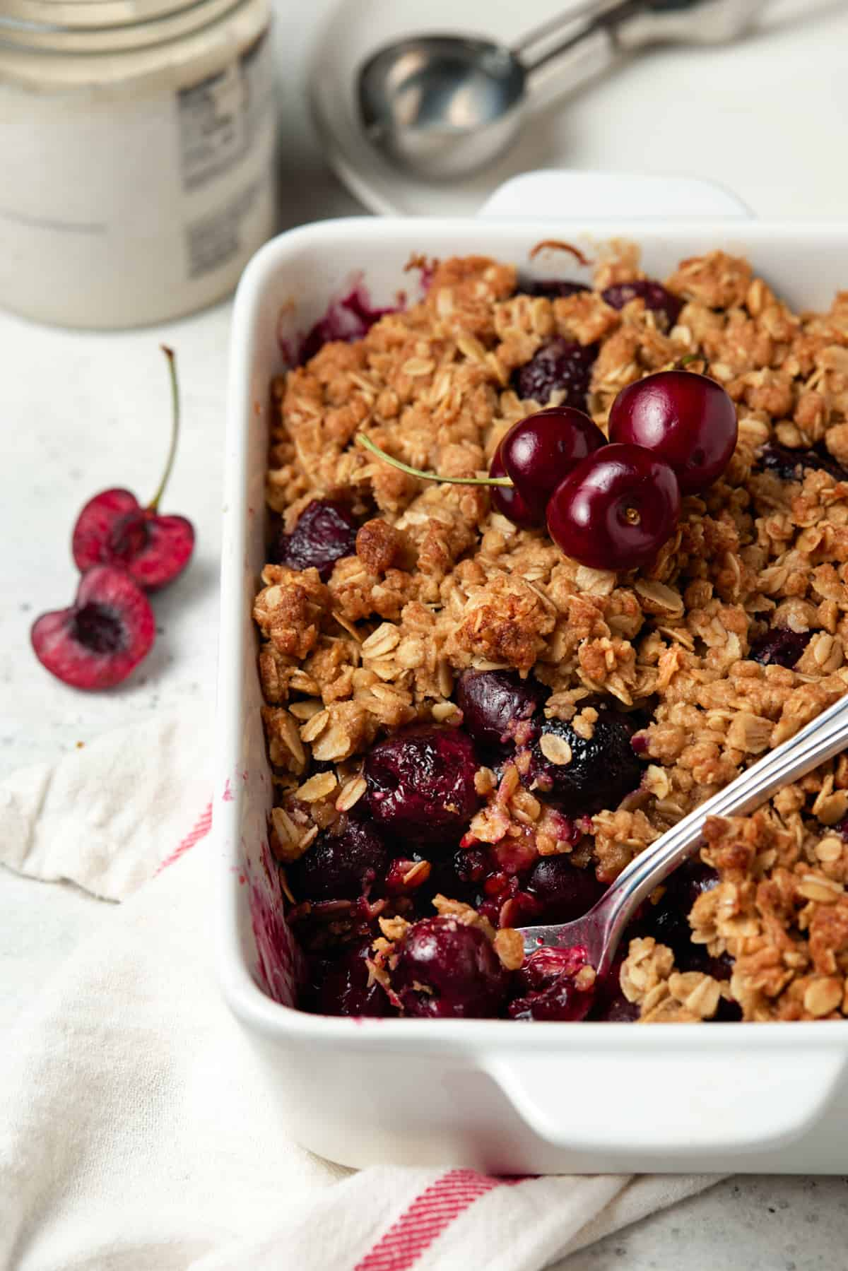 White casserole dish of baked cherry crisp with serving removed.