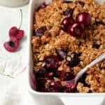 Cherry crisp in a white pan with cherries on top.