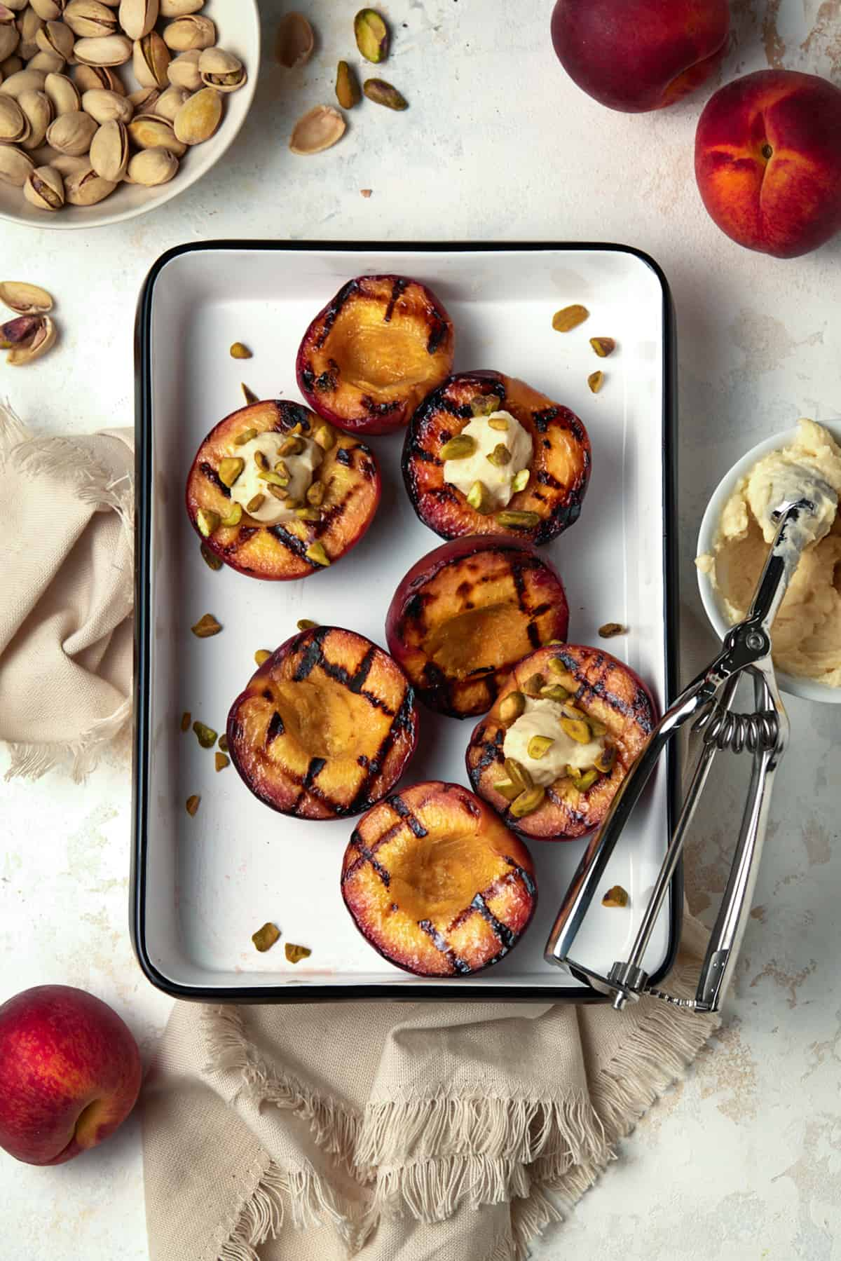 Grilled peach halves in a white enamel tray. Garnished with pistachios and mascarpone cheese.