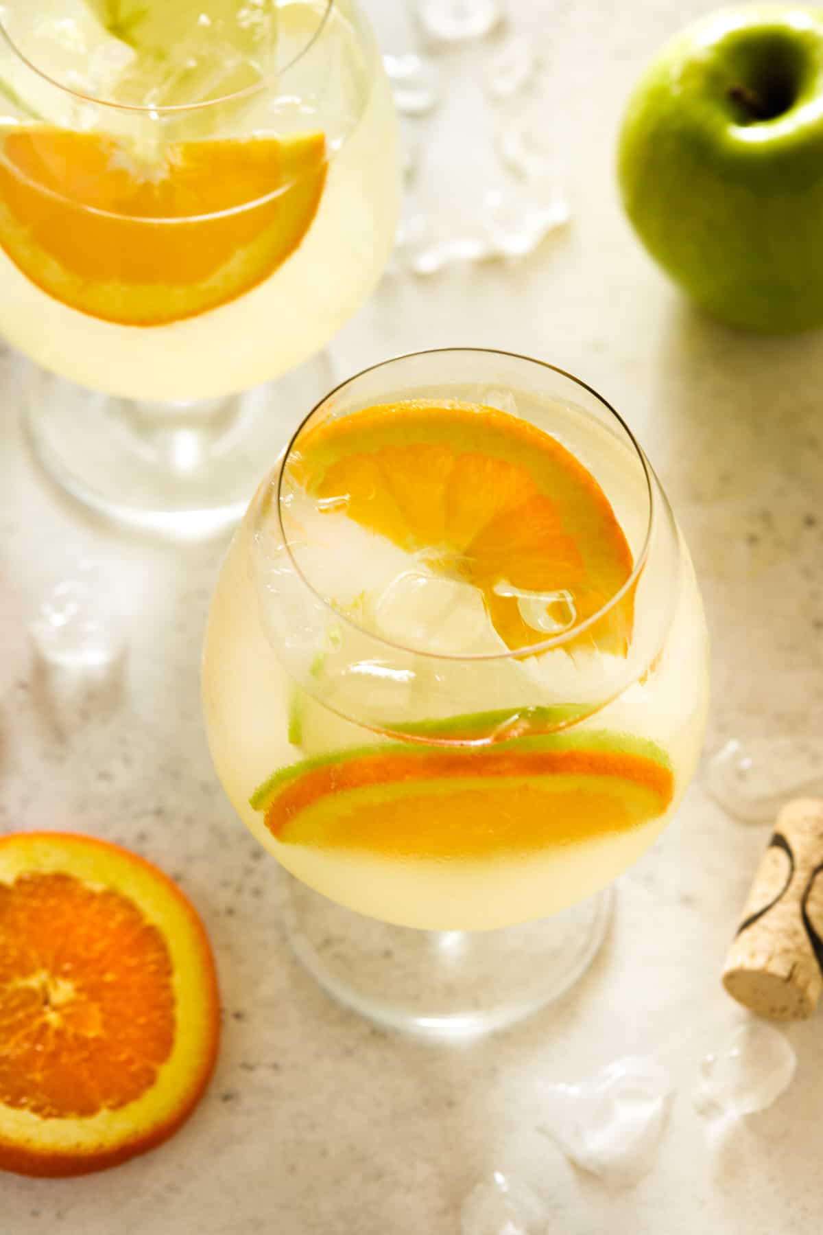 large glasses filled with lemonade and fresh orange and apple slices.