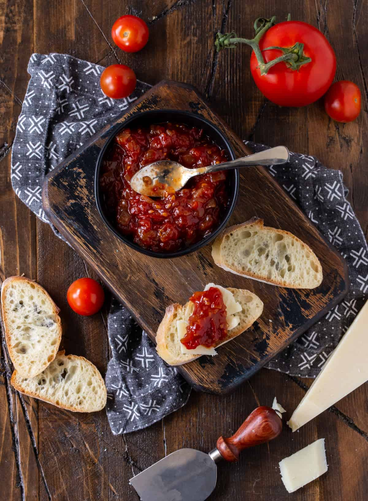 Baguette and cheese slices topped with Sweet and Tangy Tomato Jam recipe on a wooden cutting board.