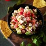 bowl full of salsa and feta cheese with chips.