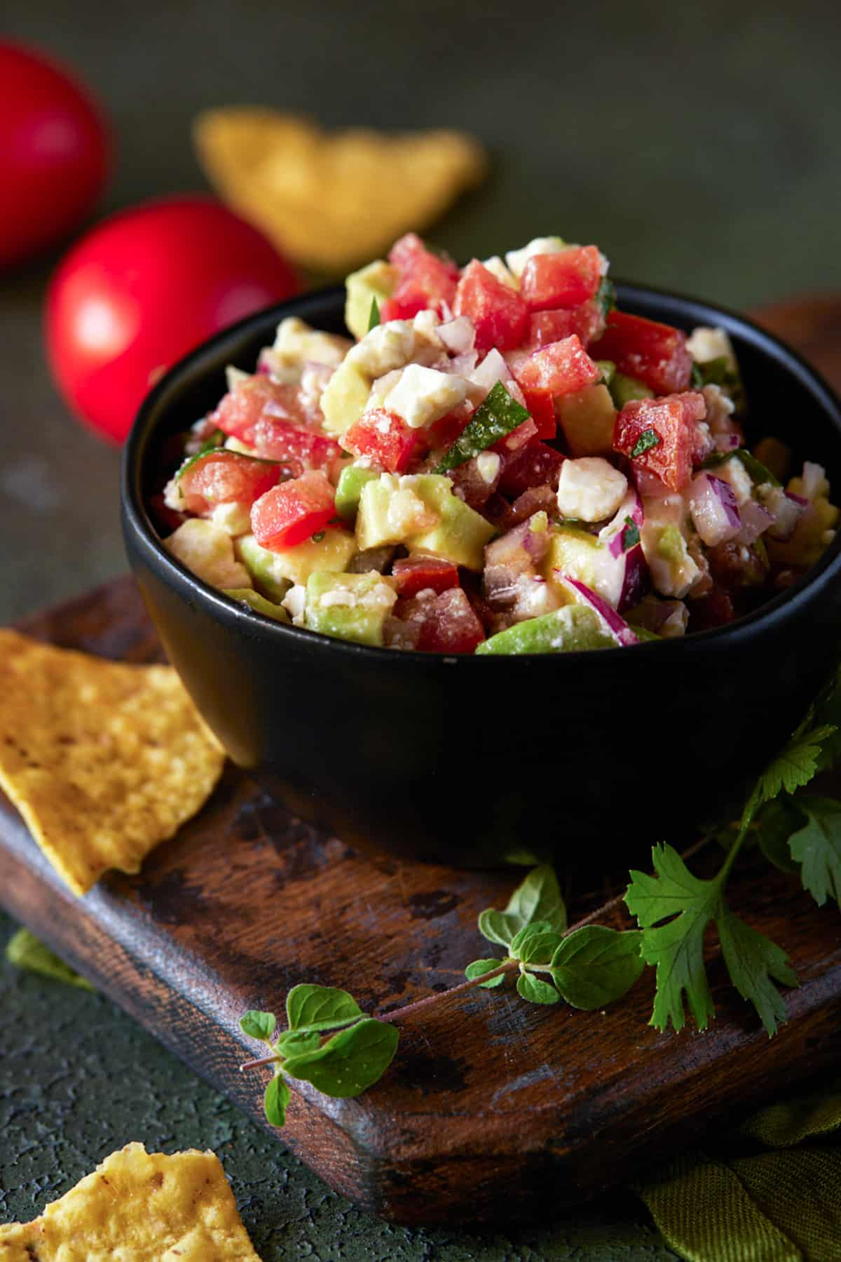 Bowl of avocado salsa wiht feta cheese on table with chips and fresh herbs.