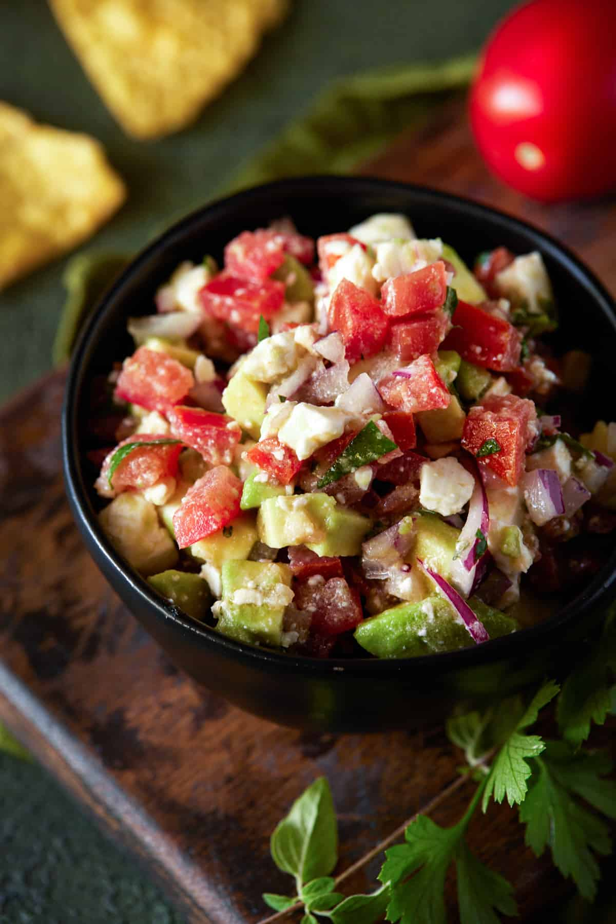 Bowl of chopped salsa and feta cheese with chips.