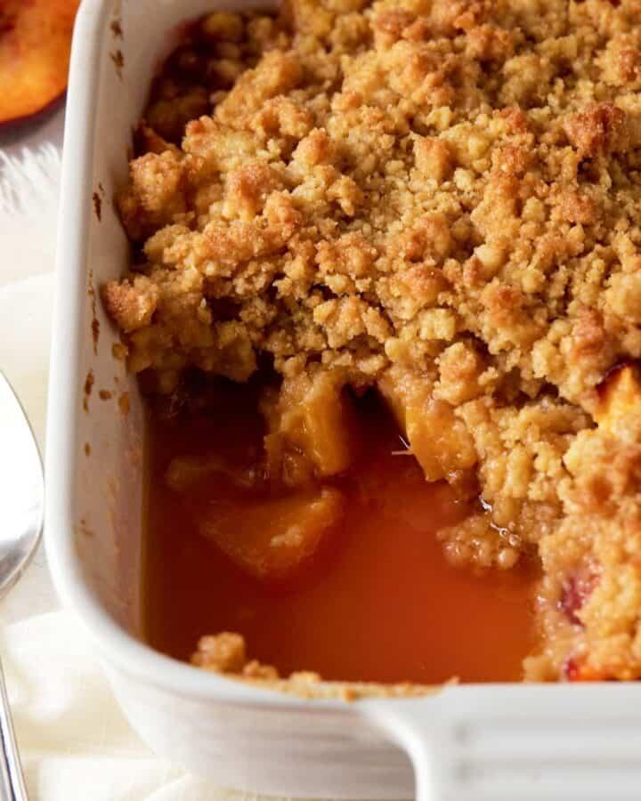 Peach crumble in white baking dish.