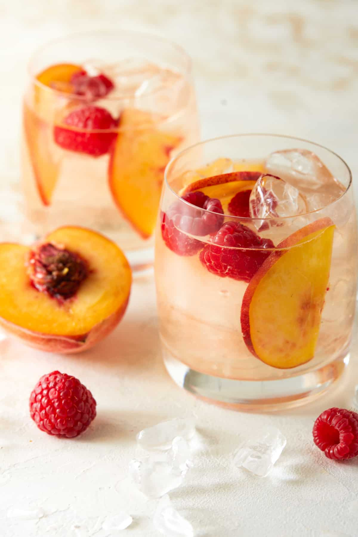 Two glasses of rosé sangria garnished with peach slices and raspberries.