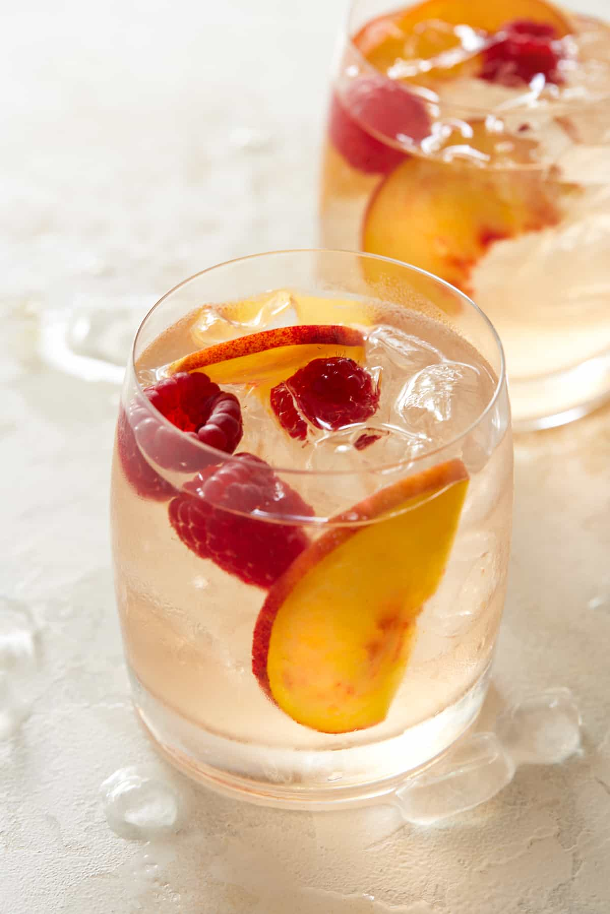 Two glasses of rosé sangria with ice, peach slices and raspberries.
