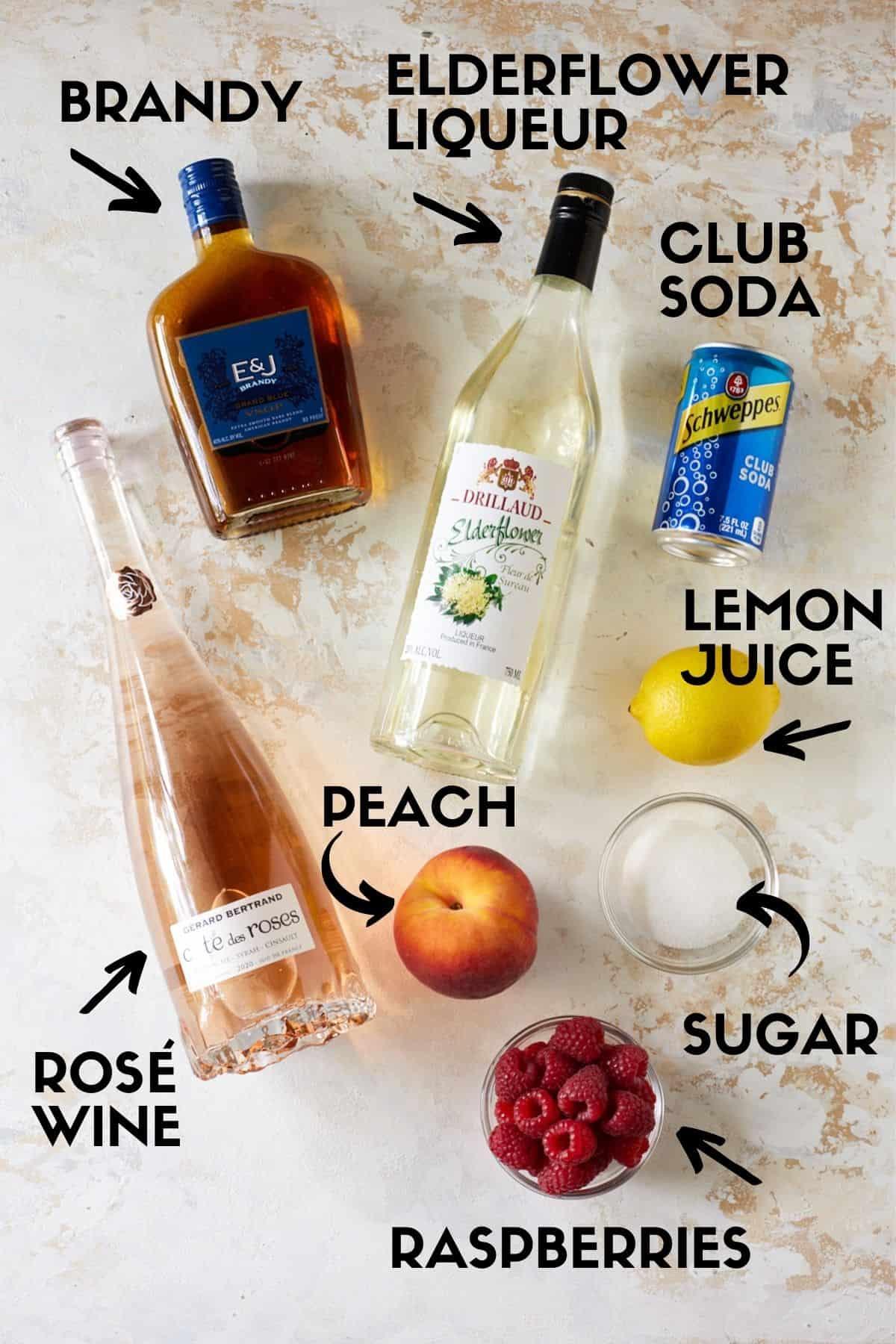 Rosé sangria ingredients, including rosé wine, elderflower liqueur, brandy, peaches and raspberries.