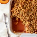 peach crumble in white baking dish with scoop out.