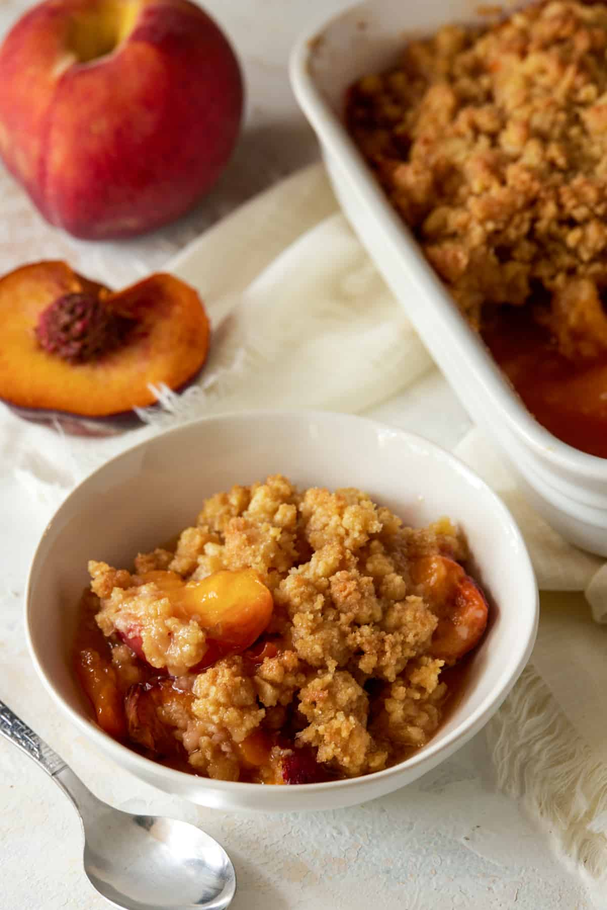 Bowl of peach crumble with baking dish.