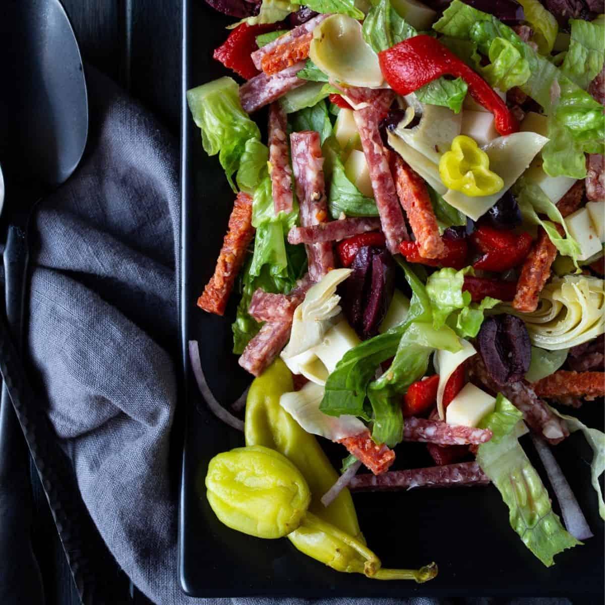 Black platter filled with antipasto salad.