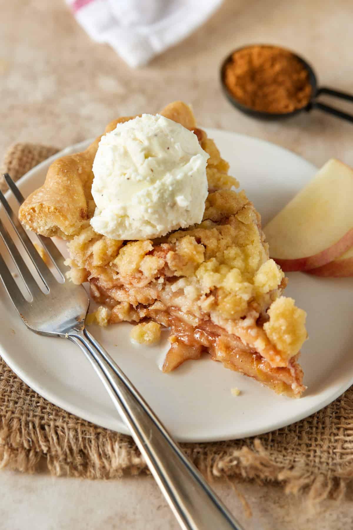 piece of apple crumble pie on plate with vanilla ice cream.