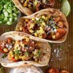crispy shrimp tacos on sheet pan with lime wedges.