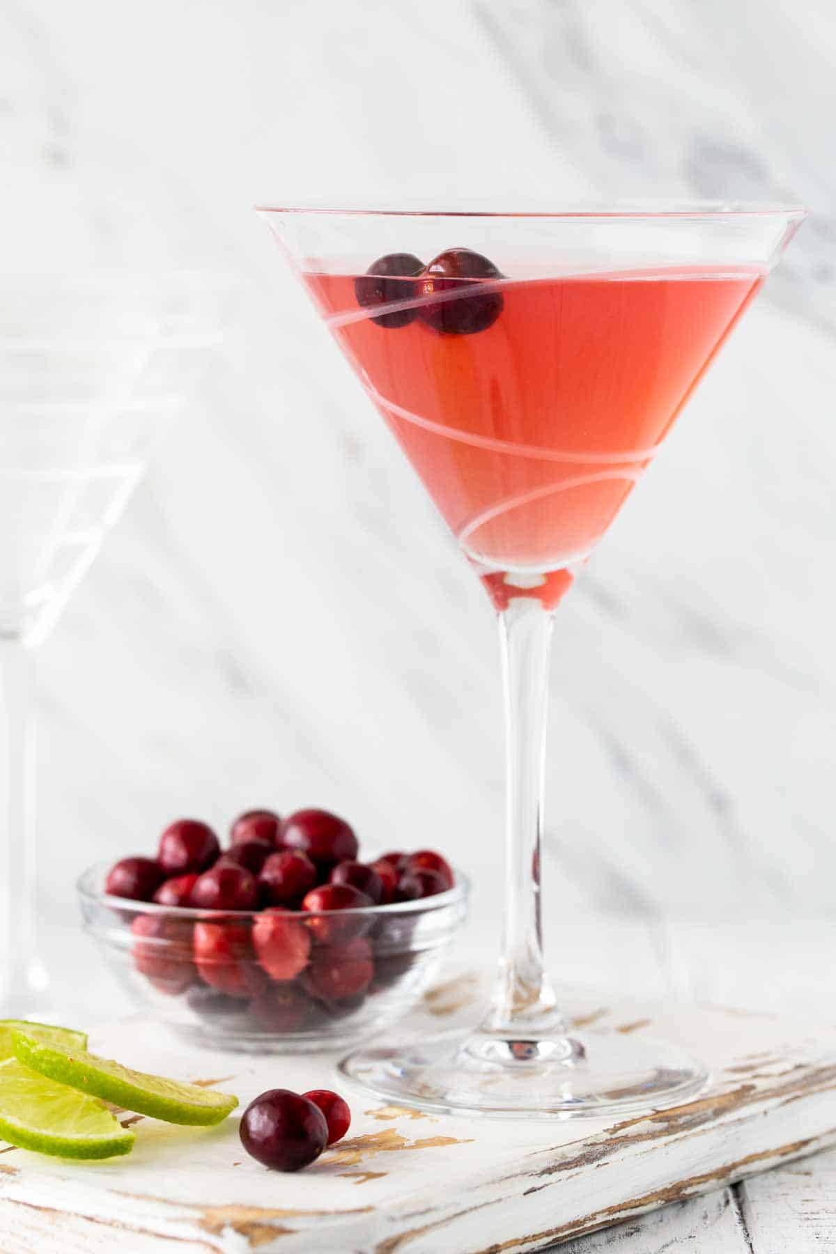 Pink martini with cranberries on a white board.