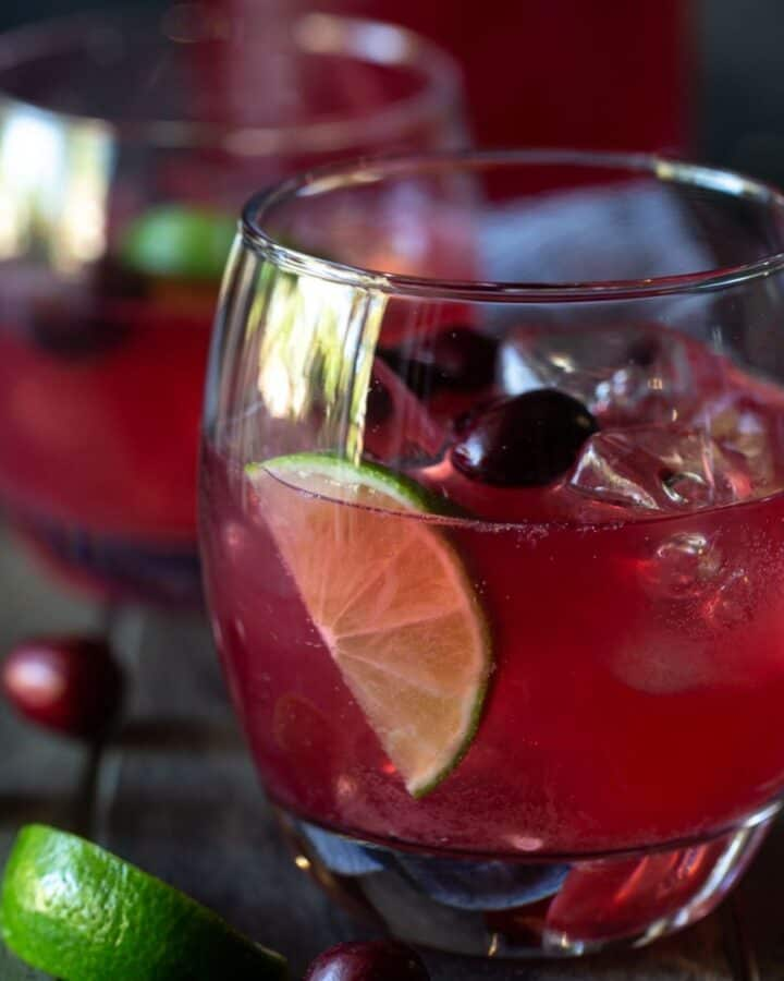 Glass of cranberry vodka punch with ice and lime wedges.