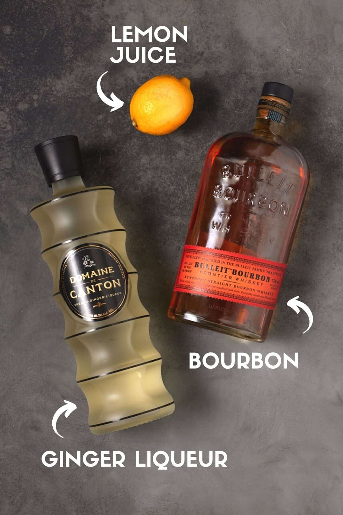 Bottles of bourbon and ginger liqueur with a lemon on a gray board.