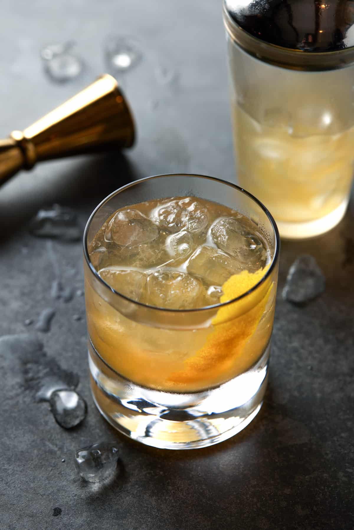 Low ball glass filled with ice and golden cocktail on a gray board.
