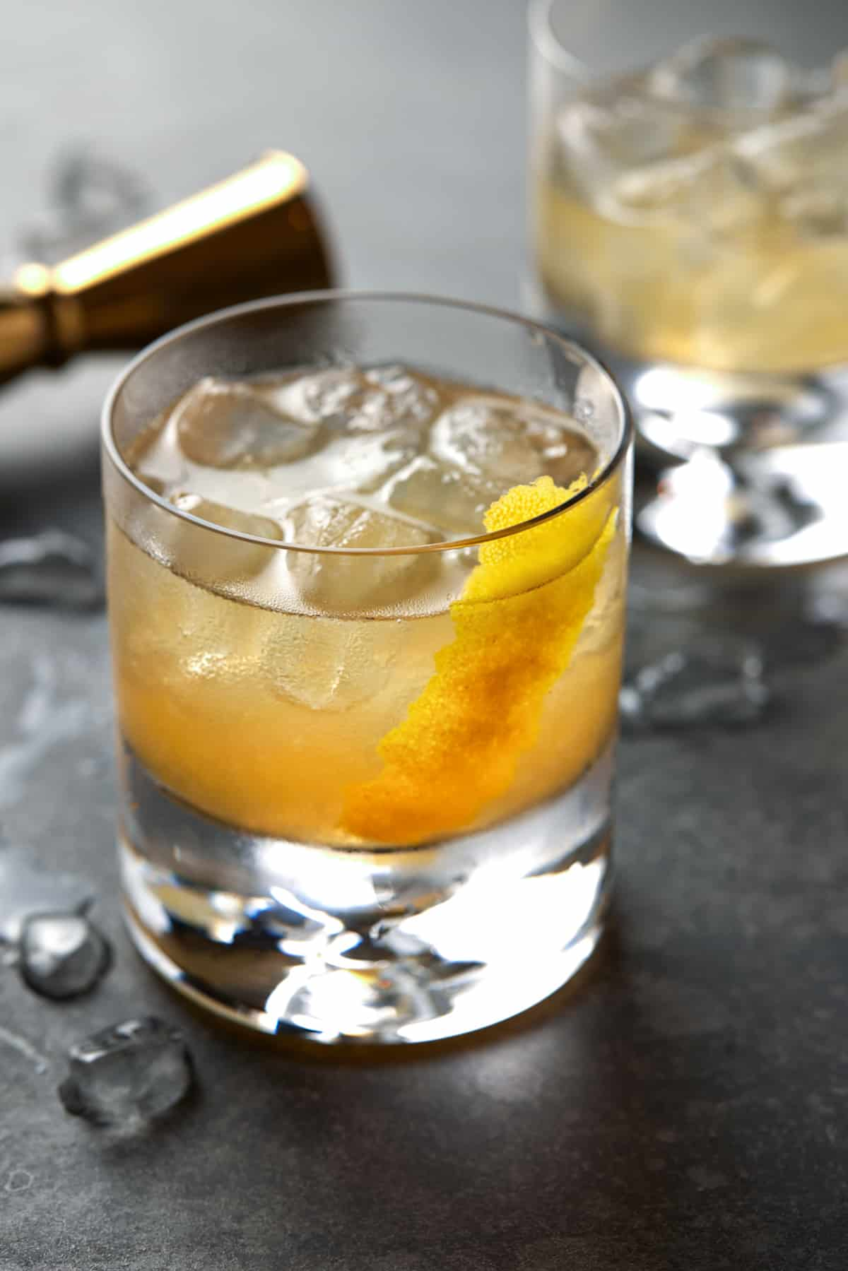 Lowball glass of golden cocktail on a dark gray board.